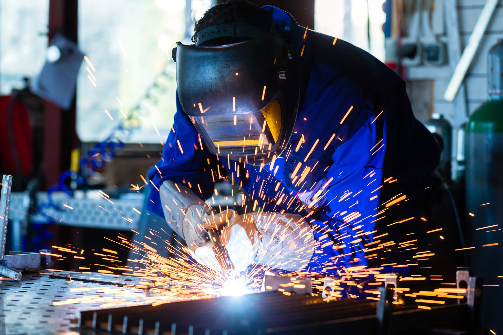 Welder welding metal in workshop with sparks.